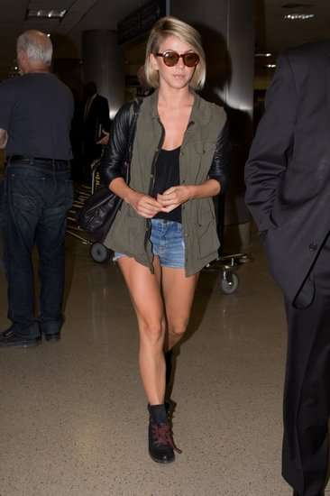 Julianne Hough worked her way through LAX airport in a leather-sleeved army jacket, black tank, denim cutoffs, lace-up boots, and round tortoiseshell sunglasses.