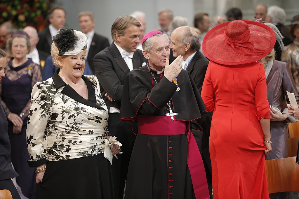 Dutch former swimming champion and former MP Erica Terpstra laughed with a priest at the royal inauguration.
