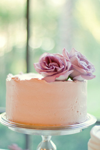 How sweet is this one-tiered blush cake topped with lavender roses? It's almost too pretty to eat (emphasis on almost) and leaves room to serve other treats like cupcakes and cake pops.  Photo by Closer to Love Photography via Style Me Pretty