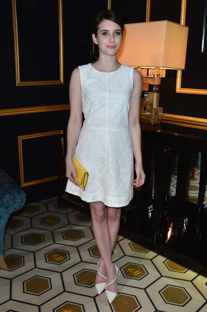 At the H&M Fall 2013 fashion show in Paris, Emma Roberts was pretty in a white fit-and-flare dress, a yellow clutch, and white Christian Louboutin pumps.