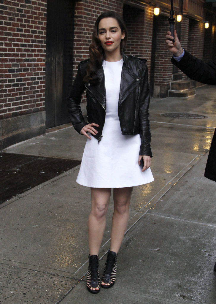 While out in NYC, Emilia Clarke's little white dress took on a tough-chick attitude thanks to her black leather biker jacket and black caged booties.