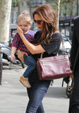 Victoria Beckham held on to her daughter Harper in Paris.