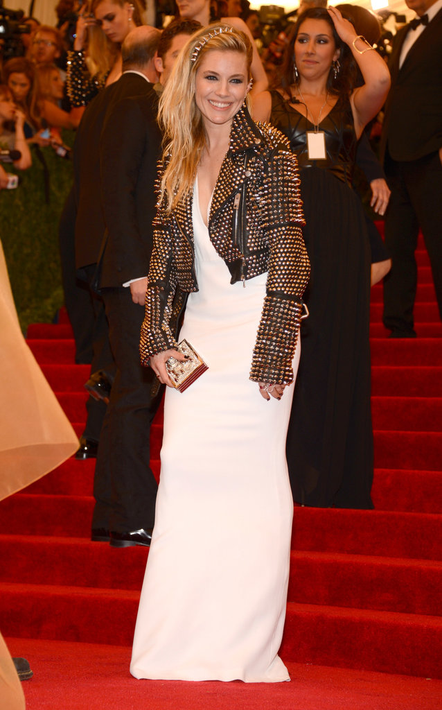 Sienna Miller topped her white gown with a studded biker jacket and a box clutch, all by Burberry, then added a Genevieve Jones ear cuff.