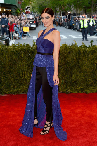 Jessica Paré paired a Jason Wu violet top over a pair of black tuxedo pants, then finished with black strappy sandals and Delfina Delettrez jewels.