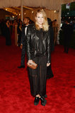 Dree Hemingway added a black leather biker jacket to her black sheer maxi dress, then added an au natural touch via a wooden clutch.