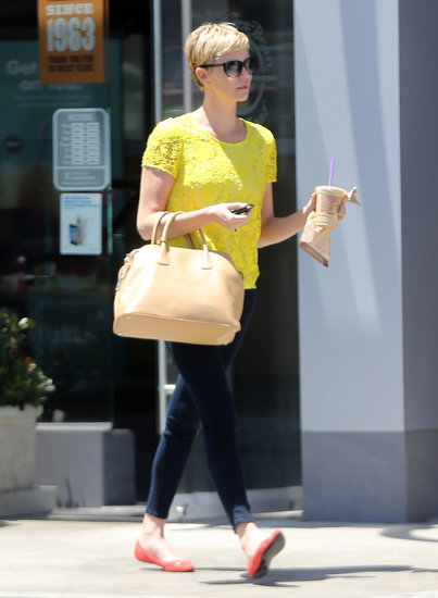 Charlize Theron tamed her bold yellow lace Madewell tee and red ballet flats with Level 99 jeans and a nude handbag in NYC.
