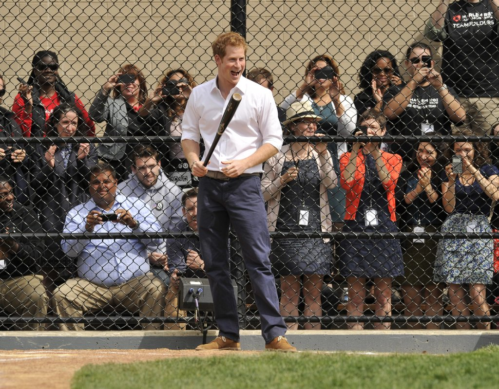 A group of fans watched Prince Harry on Tuesday while he tried his hand at baseball in Harlem, NYC.