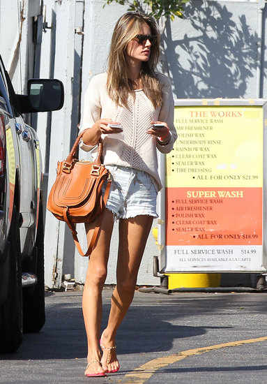 Alessandra Ambrosio put her toned legs on display in printed denim cutoffs by Citizens of Humanity, then added a crochet sweater, a tan bag, and studded t-strap sandals.