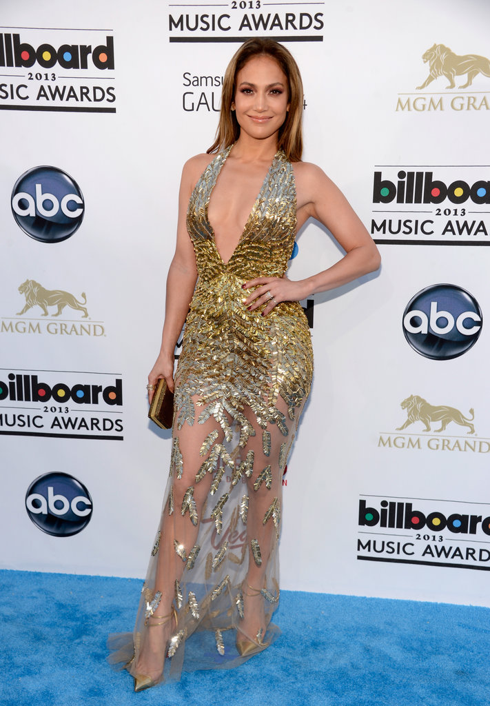 Jennifer Lopez stunned (and sparkled) in a plunging gold embellished gown with a sheer skirt and gold ankle-strap pumps.