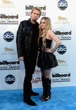 Avril Lavigne — pictured here with fiancé Chad Kroeger — was edgy in a black leather minidress and black sandal boots.