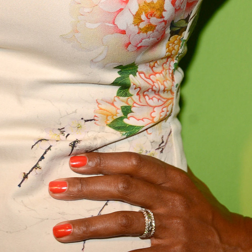 Aisha Tyler proved how eye-catching a vibrant orange hue works against an ivory dress. This would be an ideal pairing for a Summer wedding.