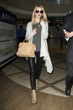 Stay warm on the plane like Rosie Huntington-Whiteley with a luxe layered approach; leather leggings, a long-line cardigan and neutral accessories.