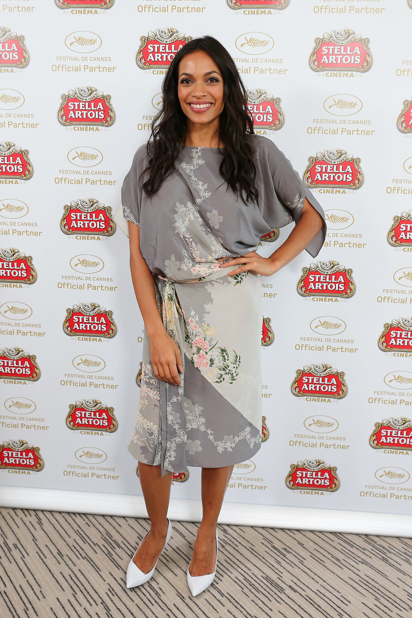 Rosario Dawson hit the Cannes Film Festival in style wearing a gray floral dress, contrasted with a pair of crisp white pumps.