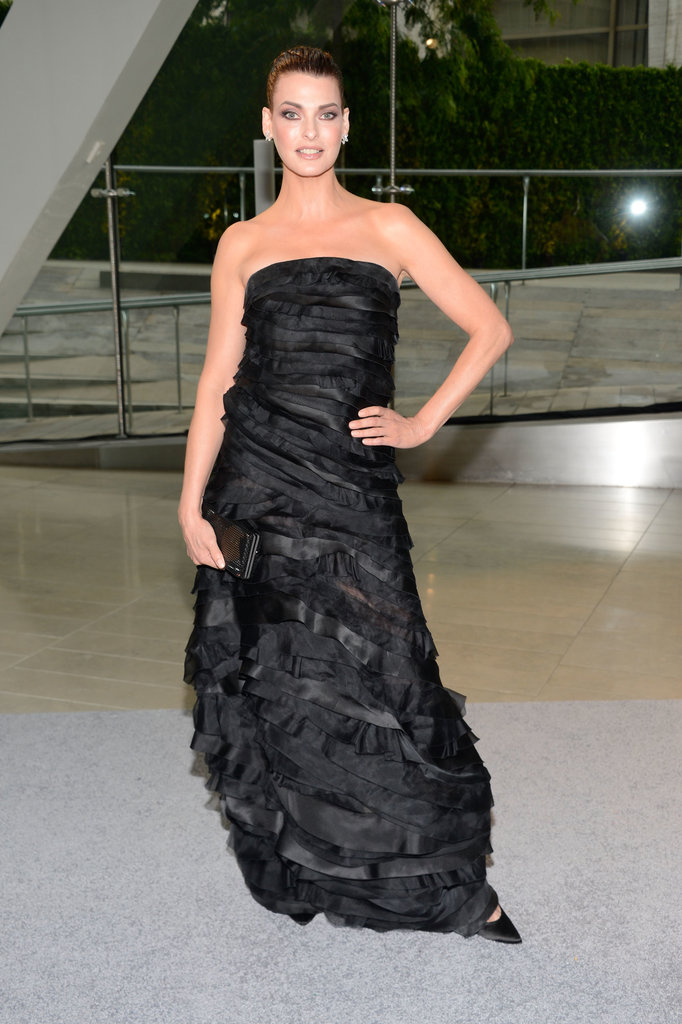 Linda Evangelista got dolled up in a black strapless tiered Oscar de la Renta gown, finished with a black clutch, Harry Winston earrings and pointy pumps.