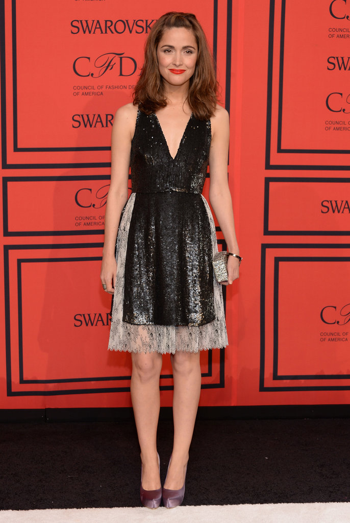 Rose Byrne balanced dainty with sassy in a black sequined v-neck Thakoon dress and purple satin pumps.