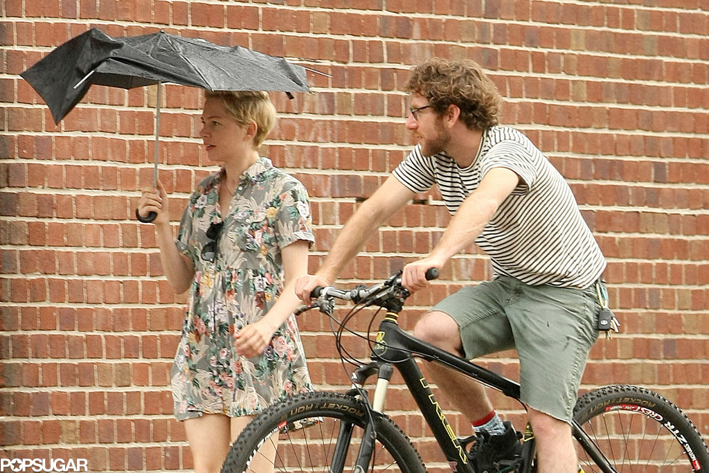 Michelle Williams held onto an umbrella while Dustin Yellin rode his bike alongside.
