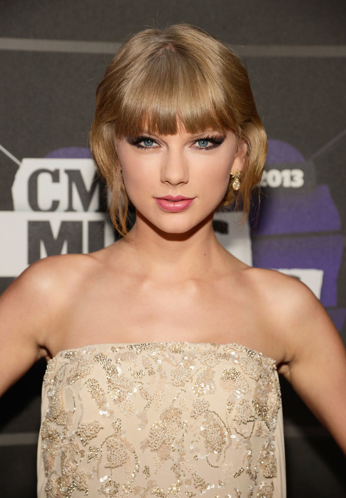 Taylor Swift was spotted on the red carpet without her signature red lipstick. The singer went for a dramatic winged smoky eye and wavy updo instead.