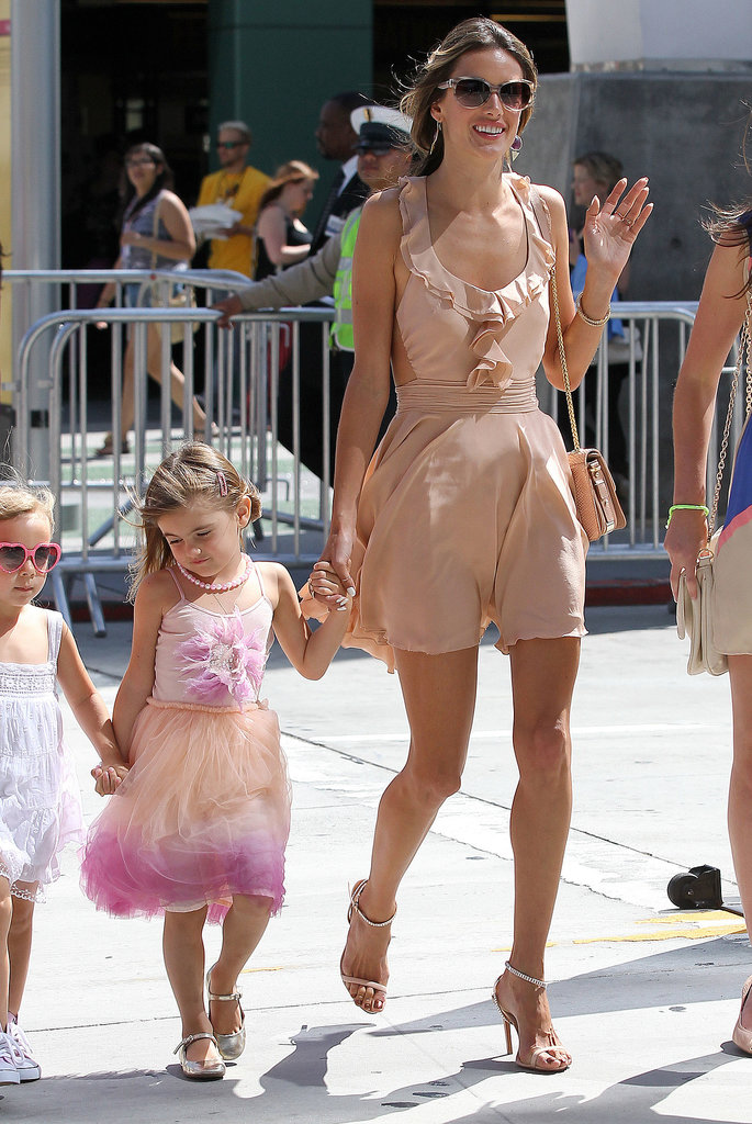 Alessandra waved in a peachy ruffled minidress and matching ankle-strap sandals in LA.