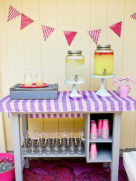 A drink station was outfitted with giant-size mason jars filled with lemonade and margaritas. Sweet daisy lids and party straws continued with the vintage theme throughout the party.  Source: Jenny Cookies