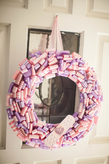 A wreath created by She's Kinda Crafty, which was made with glittery pink and purple ribbon and adorned with a large Band-Aid, greeted guests when they arrived at the party.  Source: Jenny Cookies