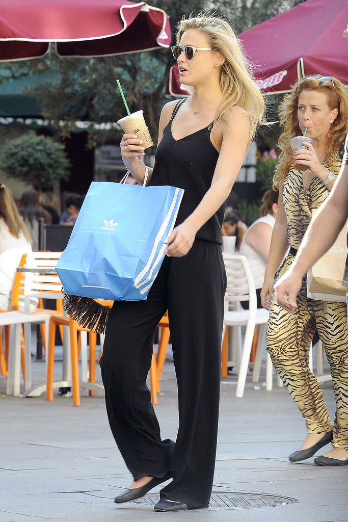 Bar Refaeli mixed comfortable with cool in a black Gypsy05 jumpsuit, white sunglasses, and black flats in Madrid.