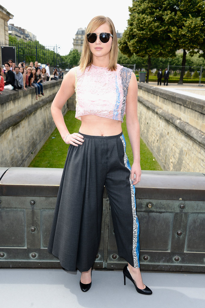 Jennifer Lawrence bared her toned midriff in a daring Dior design for the Dior Haute Couture show. She paired a pastel, metallic crop top with charcoal wool coulottes, sunglasses, black pumps, and a Bois de Rose bracelet, all by Dior.