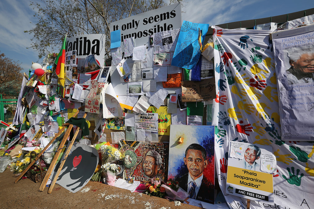 Outside the Pretoria hospital, supporters have left signs, portraits, and gifts for Mandela.