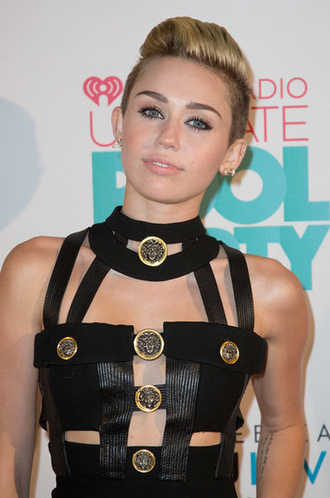 Miley Cyrus performed at the iHeartRadio Ultimate Pool Party wearing her pixie in a pompadour style, and her heavily lined lids played into her dominatrix-like ensemble.