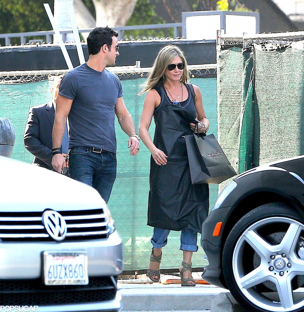 Jennifer Aniston carried a shopping bag and a garment bag.