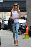 Doutzen Kroes made her skinny denim way fresh via a stark white tank, tan ankle-strap sandals, and a black MOJO DJ bag.