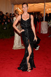 For the 2008 Met Gala, Gisele emitted a dark romantic glamour working a glittering Givenchy gown featuring a ruffle-trim thigh-baring slit.