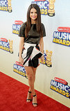 At the 2013 Radio Disney Music Awards in LA, Selena Gomez revealed her fashion prowess when she juxtaposed a tough black leather tee with a feminine, printed, tulip-shaped Blumarine miniskirt from the Fall '13 collection and dainty ankle-strap sandals.