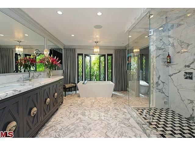 In the master bath, marble with varying scales of veining helps keep the space from feeling too sterile.