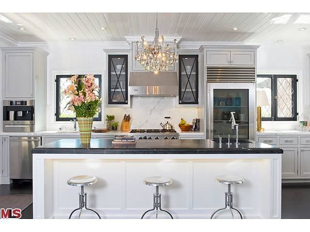 A marble backsplash, chrome stools, and a sparkling chandelier add a sense of utilitarian glamour to the kitchen.