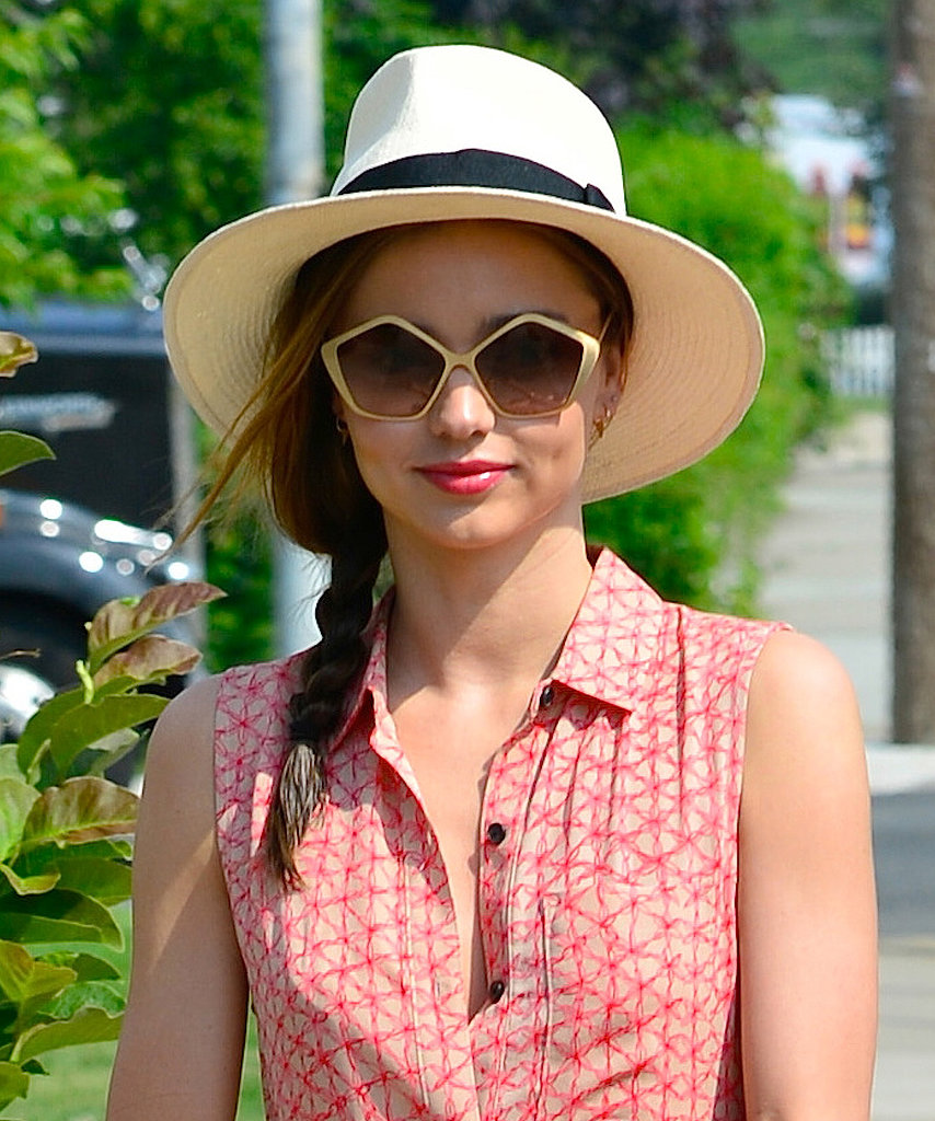 Miranda Kerr topped off her side braid with a Summer hat and completed the chic look with geometric sunglasses and a bold lip.