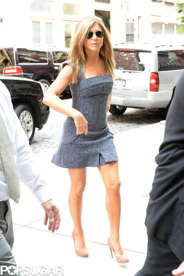 Jennifer Aniston dressed up in a short gray dress and heels.