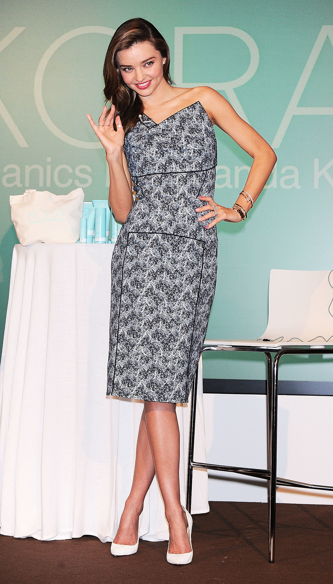 Miranda Kerr waved to fans wearing a printed bustier dress and white pumps at a Kora Organics press conference in Tokyo.
