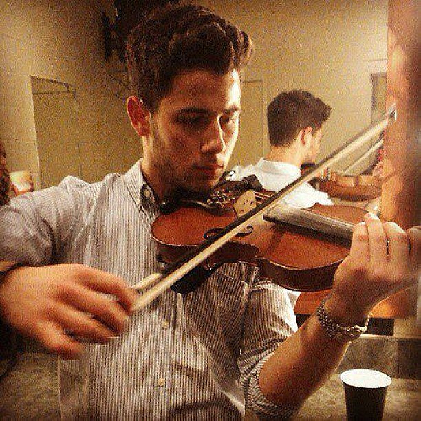 Joe Jonas snapped a photo of his brother Nick playing the violin. Source: Instagram user joejonas