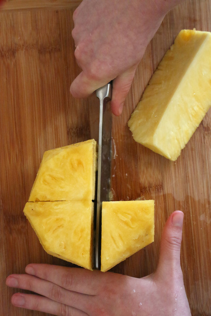 Rotate the knife 90 degrees and cut through the center again, resulting in four even pineapple pieces.