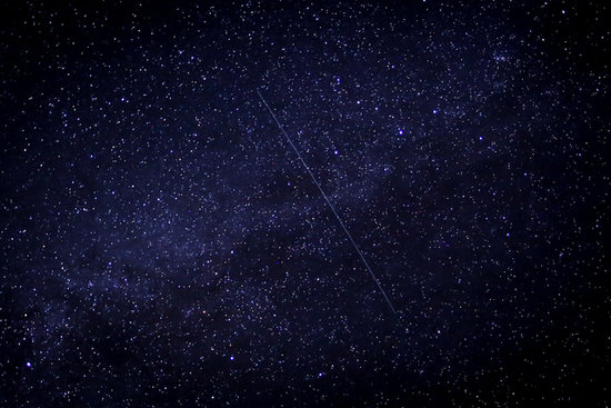 A meteor darts across the Milky Way — such a show off! Source: Flickr user D. Scott Taylor