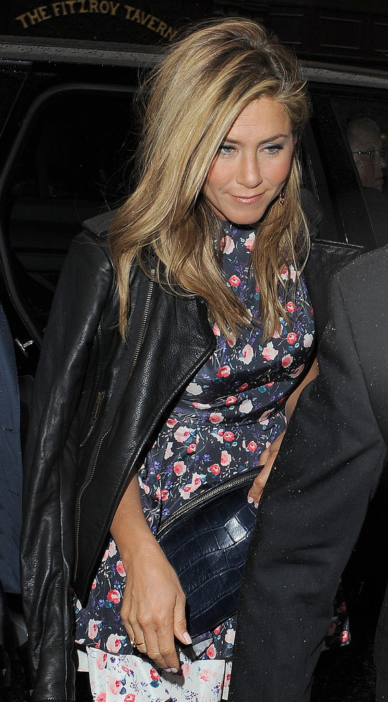 Jennifer Aniston topped her floral dress with a leather jacket for dinner in London.