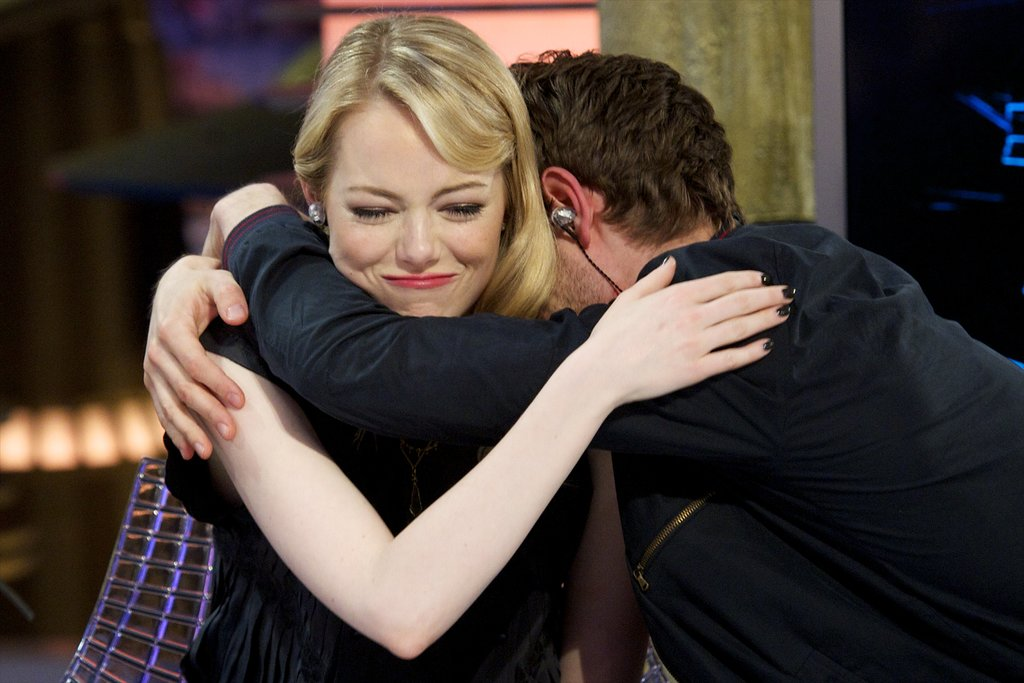 Andrew Garfield wrapped his arms around Emma Stone during a July 2012 visit to the Spanish TV show El Hormiguero in Madrid.