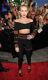 Miley Cyrus continued her love affair with crop tops on the red carpet, this time in a skintight, black, off-the-shoulder top with colorful rhinestone embellishments and matching high-waisted leggings, both vintage Dolce & Gabbana from 1992. And that's not all — she rocked more than 100 carats of Lorraine Schwartz jewels.