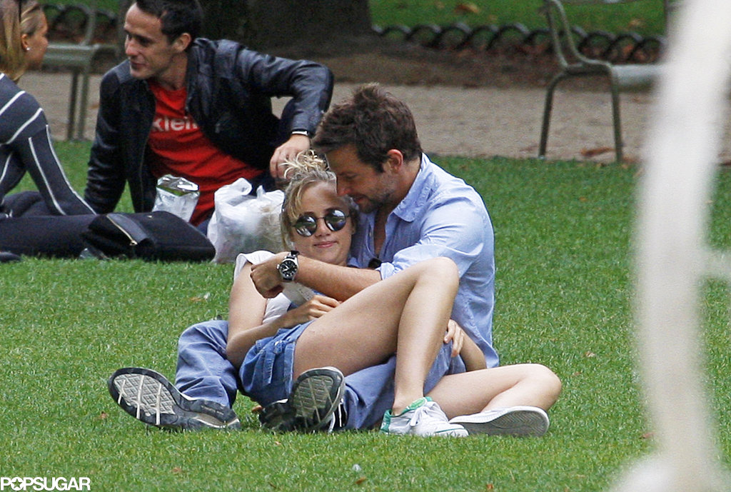 Suki Waterhouse snuggled up in Bradley Cooper's arms while the couple read a book a Paris park.