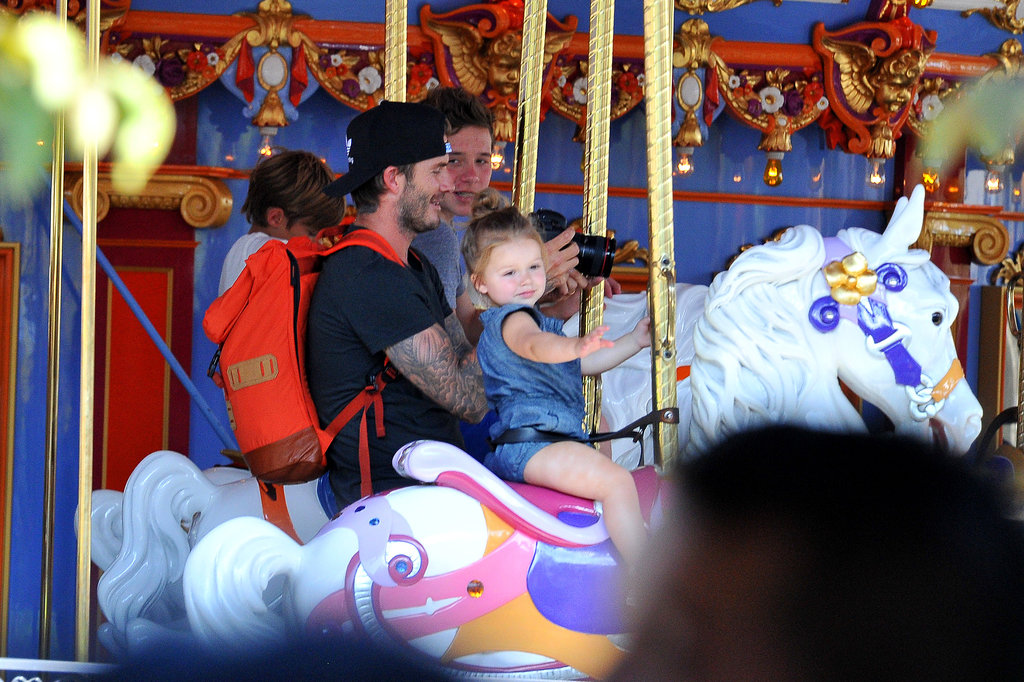 David Beckham rode the merry-go-round with his kids in August 2013.