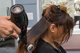"""Use a round brush to straighten your strands. """"The tension of the round brush will smooth out even curly hair types,"""" Pipino says."""