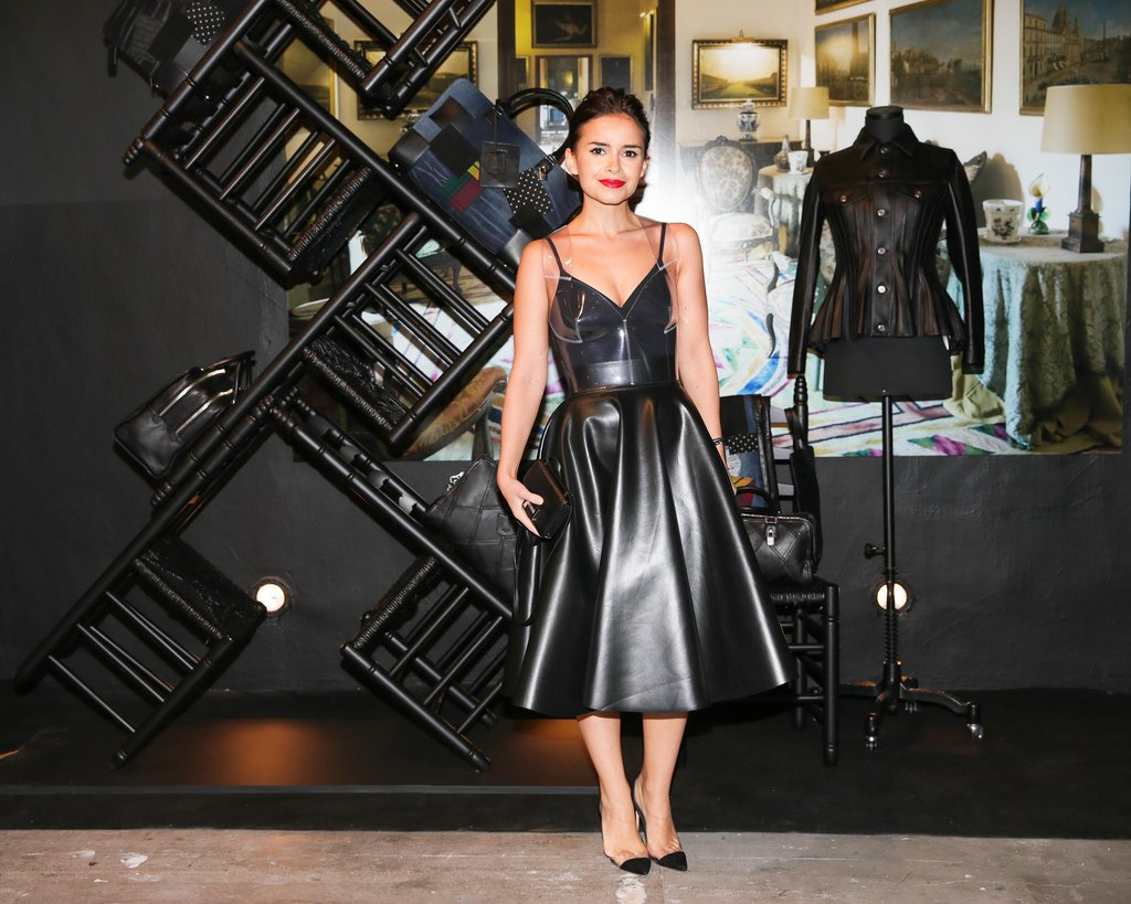 Miroslava Duma worked a black leather cocktail dress while attending the Loewe x Junya Watanabe Commes des Garcon event.