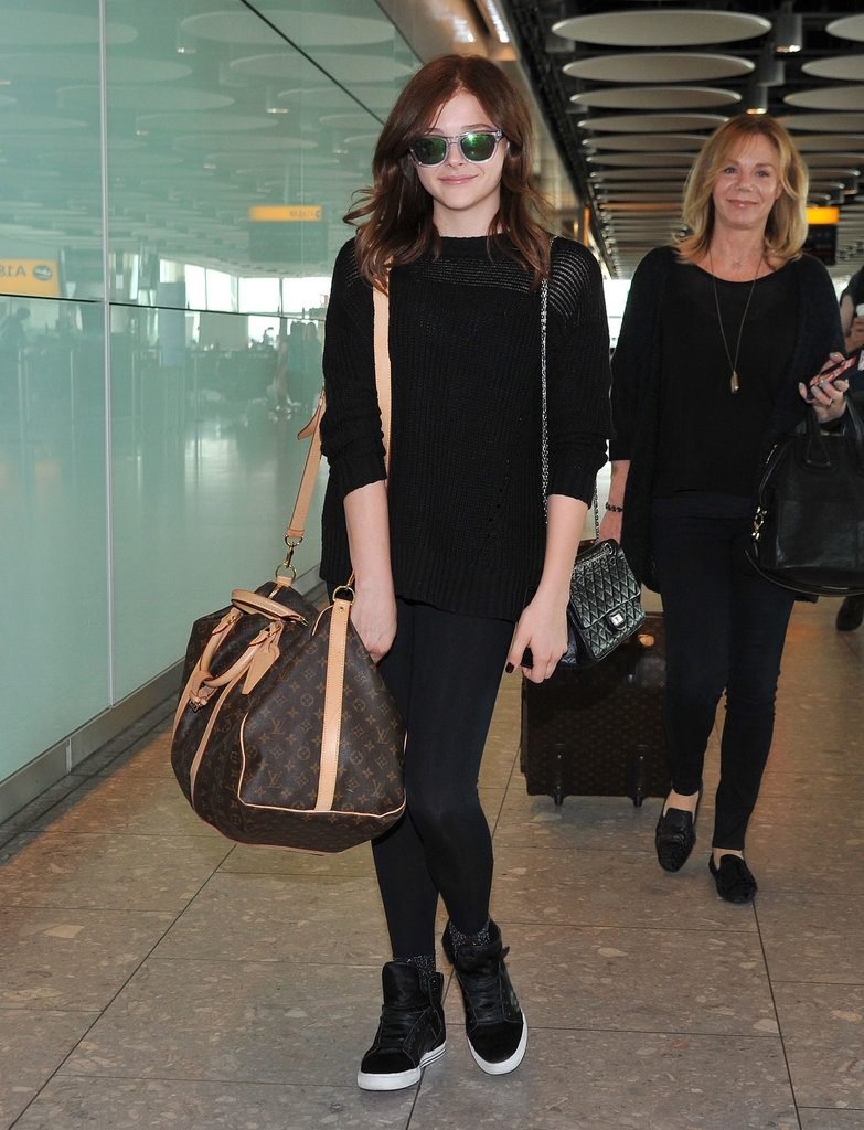 Chloë Moretz kept it all black but injected flavor via mirrored Westward Leaning sunglasses and a Louis Vuitton duffel bag in London.