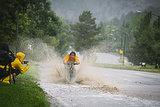 A biker moved through the flooded streets as an onlooker snapped a picture.