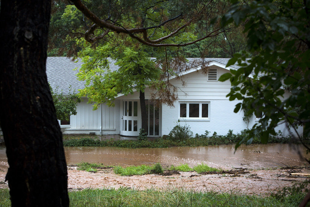 Floodwaters rose beside a house in Boulder, CO.